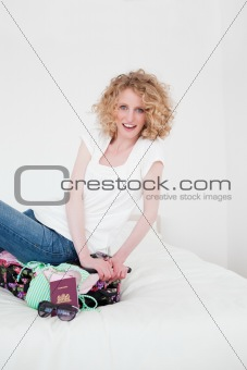 Attractive blonde female trying to close her suitcase in her bed