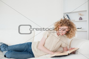 Beautiful blonde woman reading a book while lying on a sofa