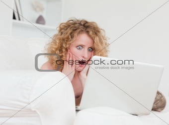 Attractive surprised female relaxing with her laptop while sitti