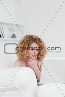 Attractive anxious female relaxing with her laptop while sitting