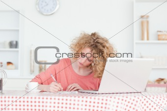 Beautiful blonde woman writing while working with her laptop in