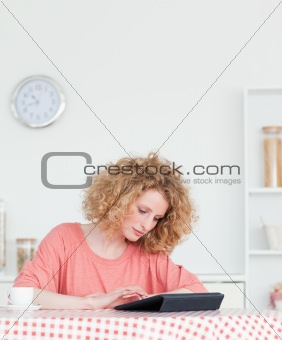 Charming blonde woman relaxing with her tablet while sitting in