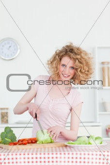 Beautiful blonde woman cooking some vegetables in the kitchen
