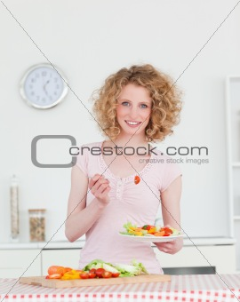 Attractive blonde woman eating some vegetables in the kitchen