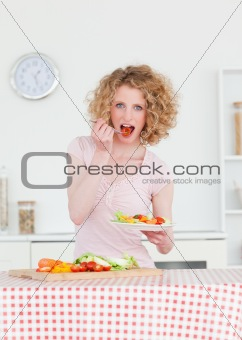 Beautiful blonde woman eating some vegetables in the kitchen