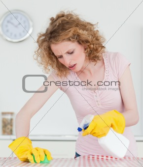 Beautiful red-haired woman cleaning a cutting board in the kitch