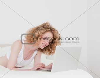 Attractive blonde woman relaxing with her laptop while lying on