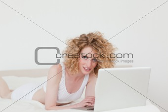 Charming blonde woman relaxing with her laptop while lying on he
