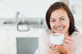 Close up of a smiling brunette having a coffee