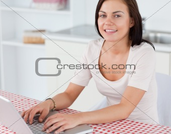 Close up of a smiling woman with a laptop