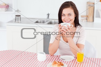 Charming brunette having her breakfast
