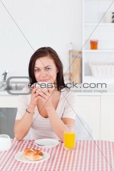 Smiling brunette having her breakfast
