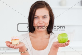 Charming brunette with an apple and a piece of cake