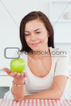 Smiling brunette showing an apple