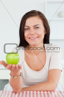 Charming brunette showing an apple