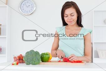 Cute woman slicing a pepper
