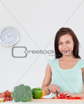 Charming woman slicing a pepper
