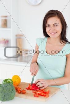 Charming brunette slicing a pepper