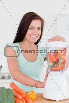 Charming dark haired woman using a blender