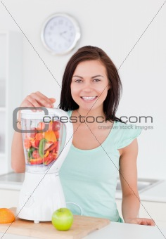 Charming woman posing with a blender