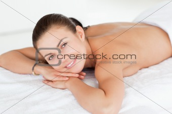 Close up of a woman lying on a massage table looking at the came