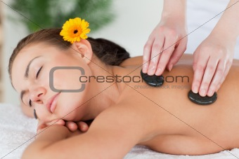 Close up of a beautiful woman enjoying a hot stone massage