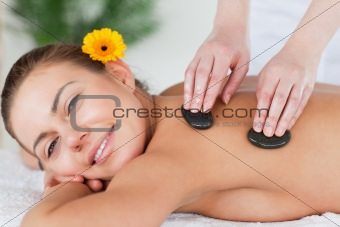Close up of a smiling woman enjoying a hot stone massage