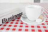 A cup of tea and a newspaper on a tablecloth