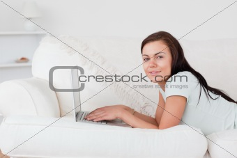 Cute woman on a sofa with a laptop