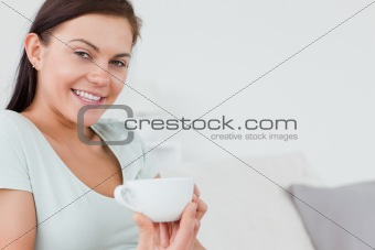 Close up of a brunette sitting on a sofa with a cup of coffee