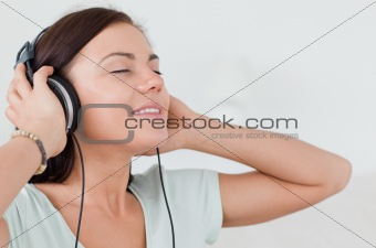 Close up of a charming brunette listening to music