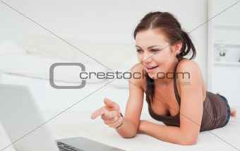 Cute woman pointing at the screen of her laptop