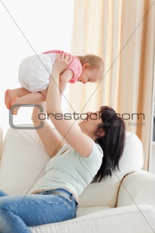 Gorgeous woman holding her baby in her arms while sitting on a s