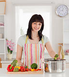 Beautiful brunette woman posing while cooking vegetables
