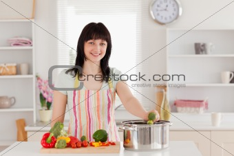 Attractive brunette woman posing while cooking vegetables
