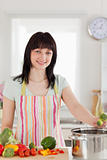 Good looking brunette woman posing while cooking vegetables