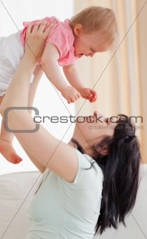 Cute woman holding her baby in her arms while sitting on a sofa