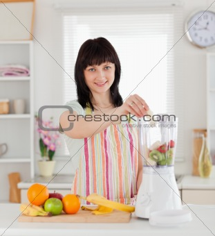 Beautiful brunette woman putting vegetables in a mixer while sta