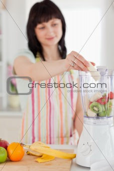 Charming brunette woman putting vegetables in a mixer while stan