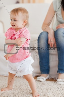 Baby standing on a carpet while her mother is sitting on a sofa