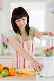 Pretty brunette woman using a mixer while standing