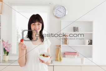 Charming brunette female eating a cherry tomato while holding a