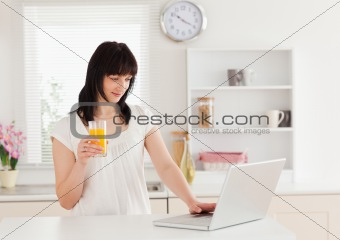Beautiful brunette woman holding a glass of orange juice while r