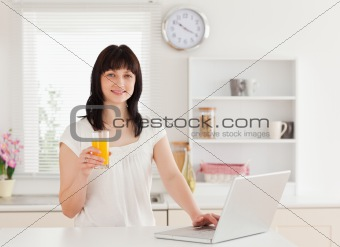 Attractive brunette woman holding a glass of orange juice while