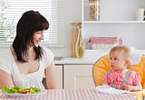 Gorgeous brunette woman having a meal with her baby while sittin