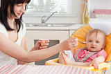 Attractive brunette woman feeding her baby while sitting