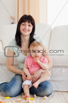 Beautiful woman holding her baby in her arms while sitting on a