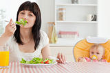 Attractive brunette woman eating a salad next to her baby while
