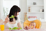 Beautiful brunette woman eating a salad next to her baby while s