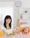 Pretty brunette woman eating a salad next to her baby while sitt